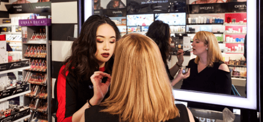 Woman applying makeup to customer